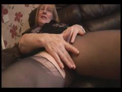 Blonde granny in pantyhose does a little striptease and rubs pussy